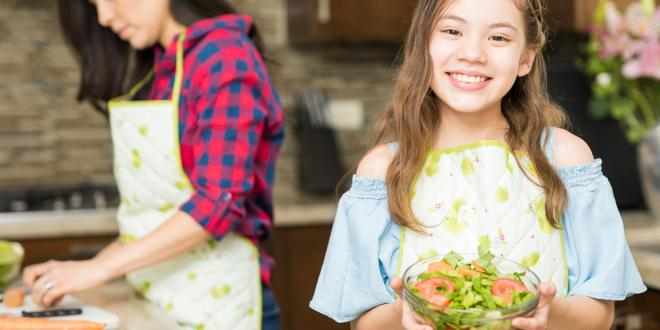 A girl holding a fresh made salad.