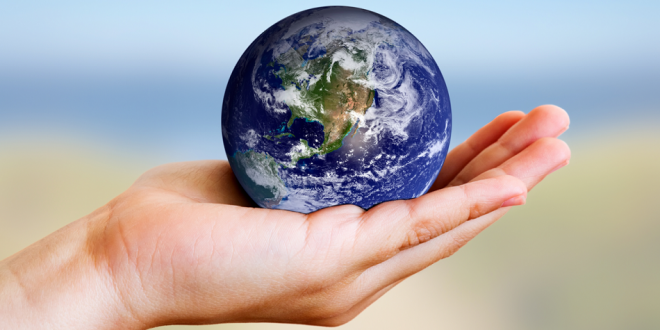A hand gently holding the Earth